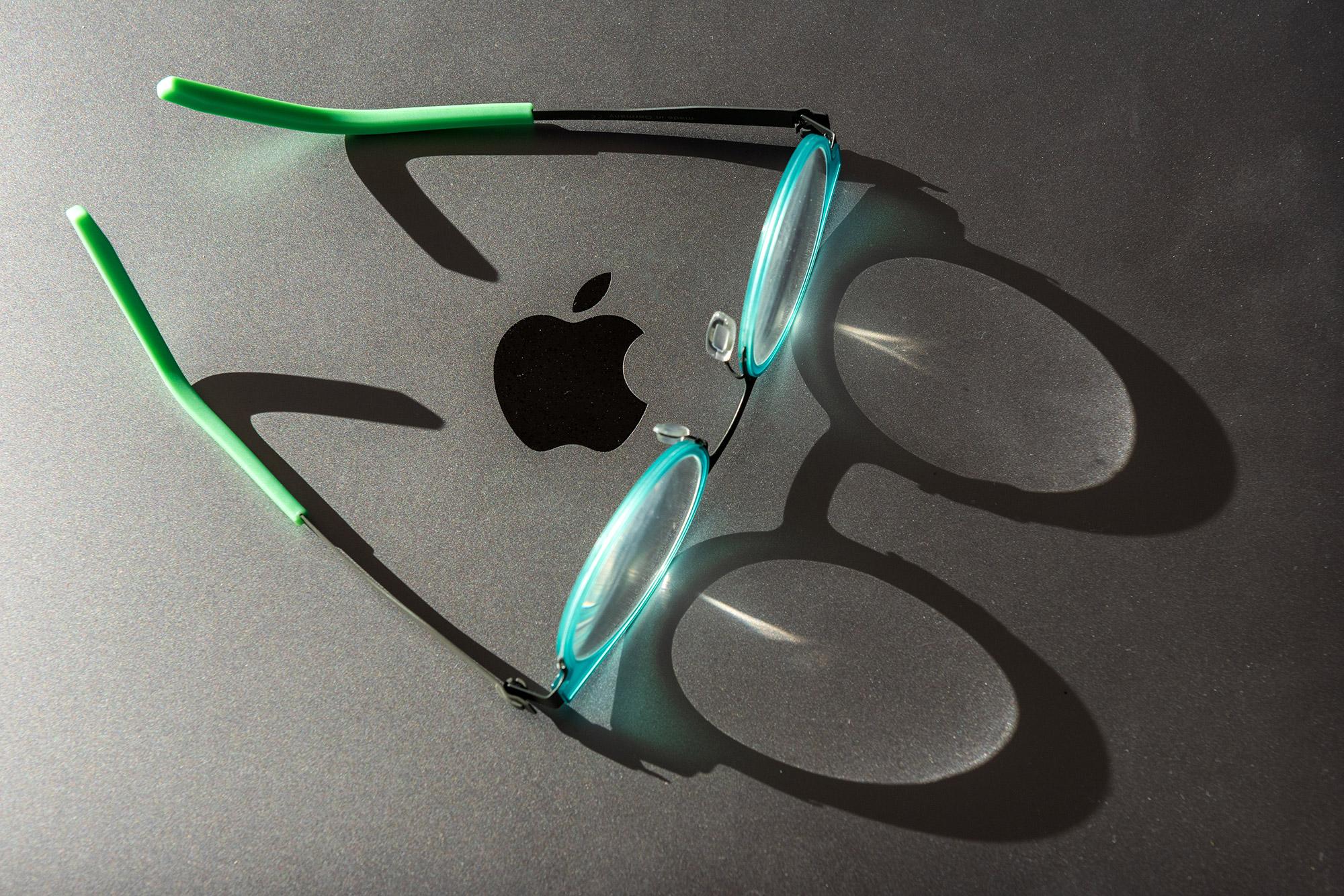 Abgelegte Brille auf einem MacBook mit Lichtspiel