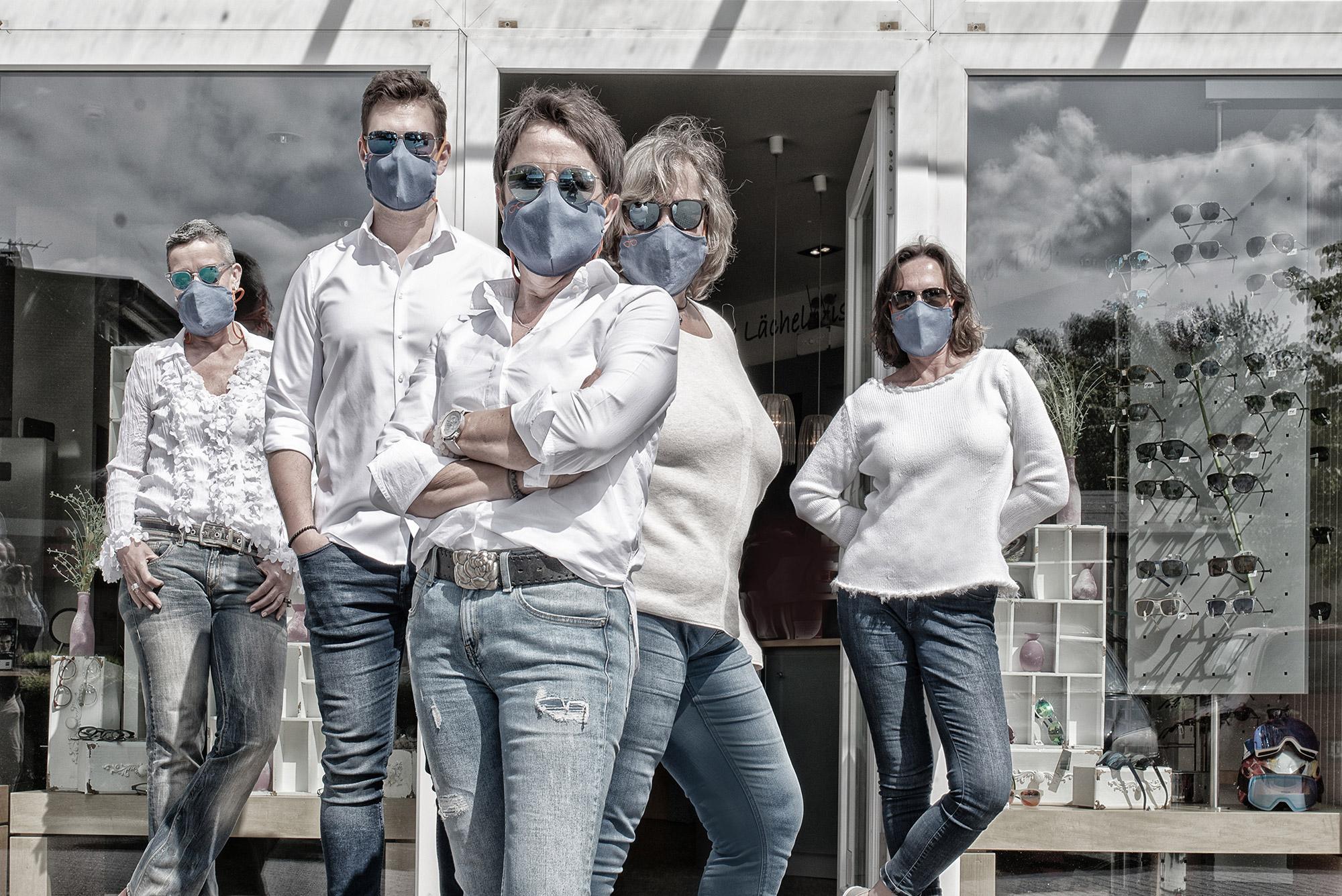 Personal posiert vor dem Geschft mit Schutzmasken