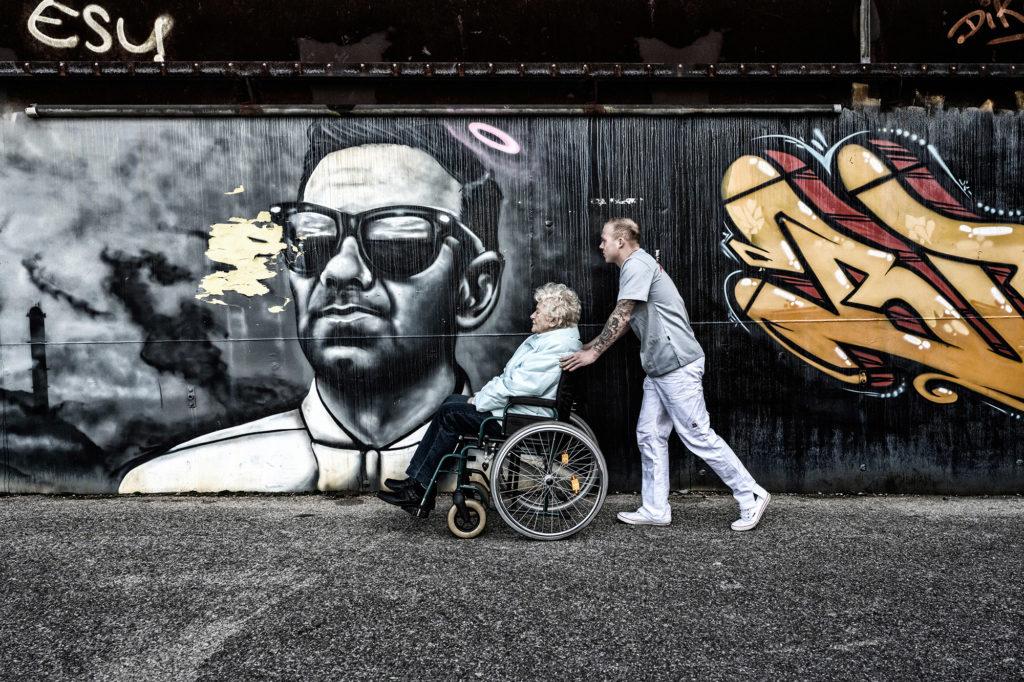 Junger Pfleger kümmert sich um eine Kundin im Rollstuhl