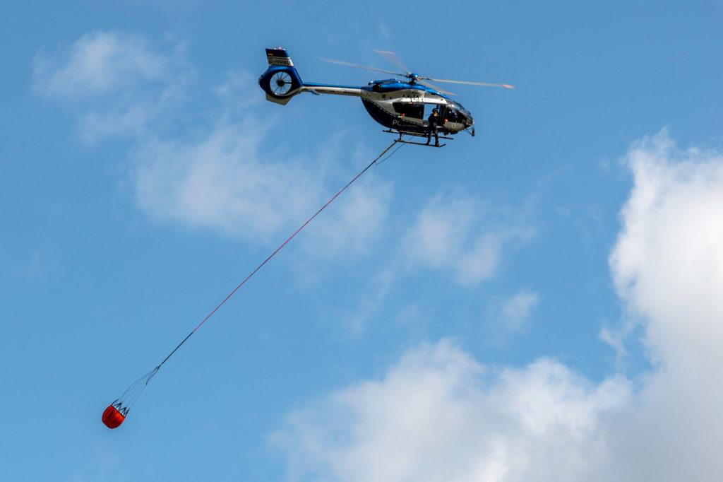 Polizeihubschrauber transportiert einen der neuen Löschwasserbehälter zur Bekämpfunf von Wald- und Flurbränden
