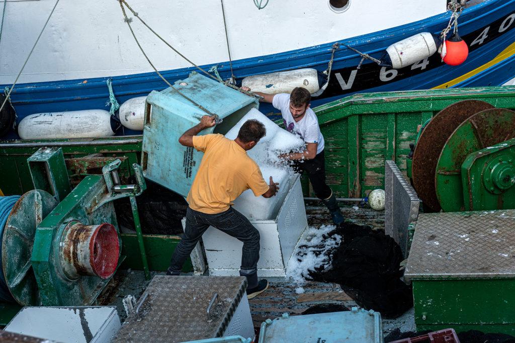 Ein Fischtrawler wird im Fischereihafen von St. Guénolé im Westen der Bretagne mit Eis zur Kühlung des Fangs beladen