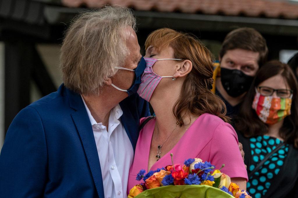 Ironie in Zeiten des Corona-Virus: Hochzeitspaar küsst sich mit Atemschutzmaske