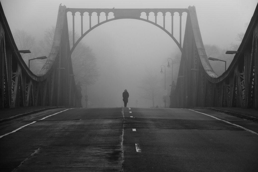 Auf der Glienicker Brücke am 11. Januar 2016. Es ist neblig und steht mit der in der Mitte der Brücke platzierten Person für den Agentenaustausch während des kalten Krieges zwischen Ost und West