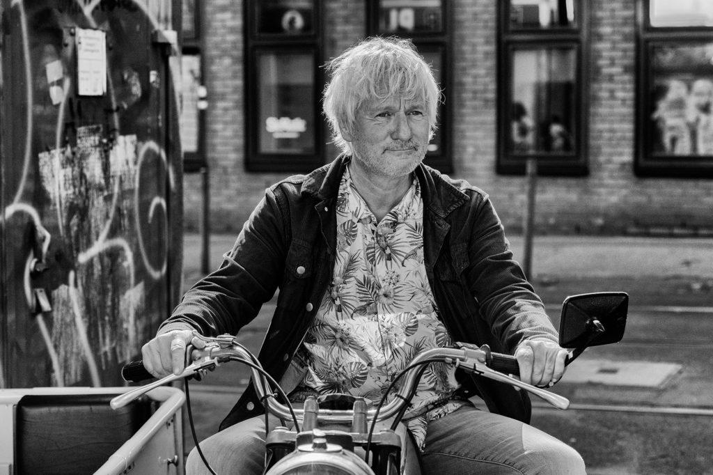 Der Kabarettist Jürgen Becker posiert für die Presse auf seinem Motorrad aus DDR-Zeiten mit Seitenwagen, mit dem er regelmäßig den Osten Deutschlands besuchte