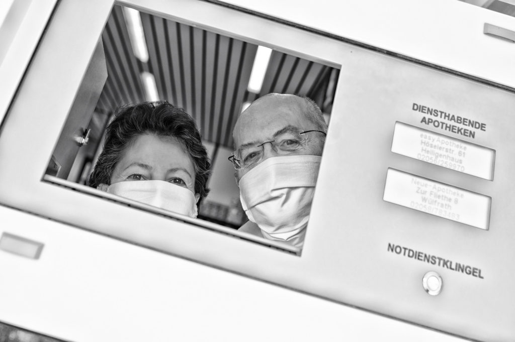 Die Klappe des Notschalters einer Apotheke mit mundgeschütztem/r Mitarbeiter/in