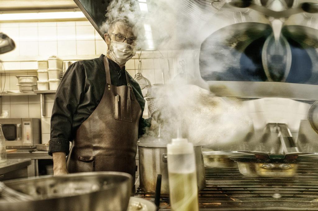 Koch am Herd in der Küche eines Restaurants mit Mundschutz