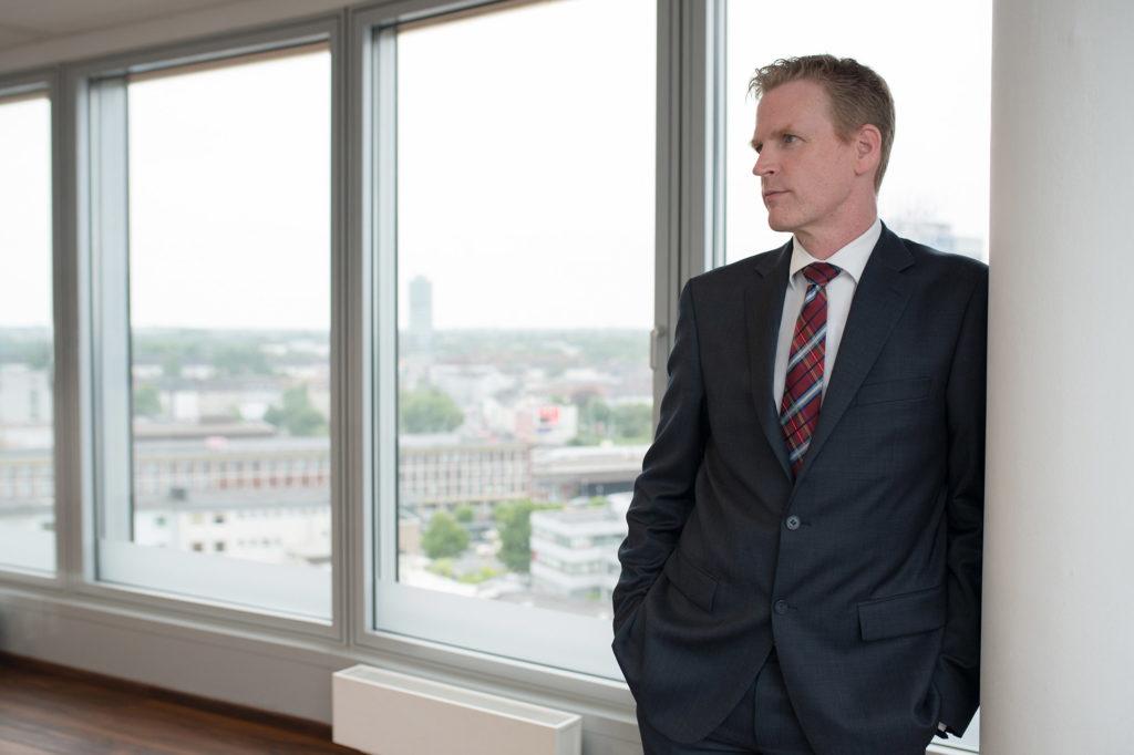 Lässig steht der Geschäftsführer eines Unternehmens an die Wand neben dem Fenster gelehnt